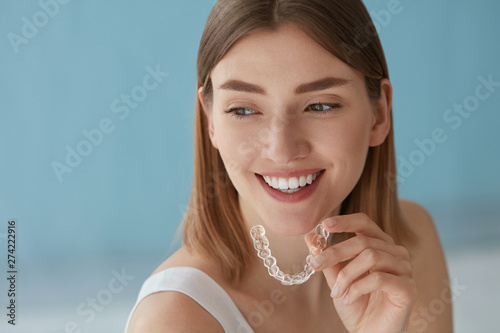 Fotografia  Teeth whitening. Woman with healthy teeth using removable braces