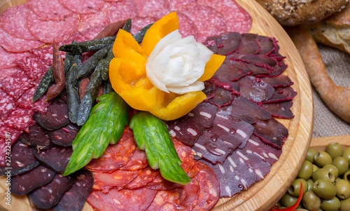 Fotografia sliced assorted cured meat and sausages decorated with carved flowers of vegetab
