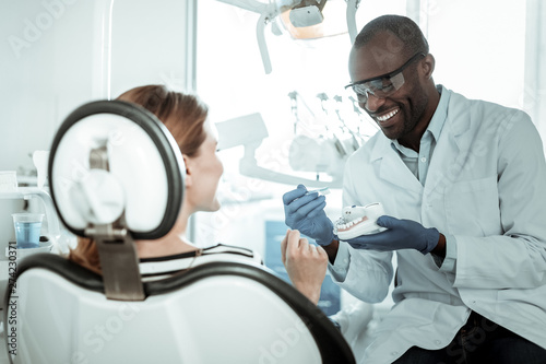 Fotografija Openly-smiling dentist carrying plastic model of the jaw
