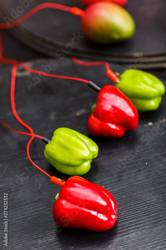 Photo Photo of red and green pepper, avocado with red wires on black table