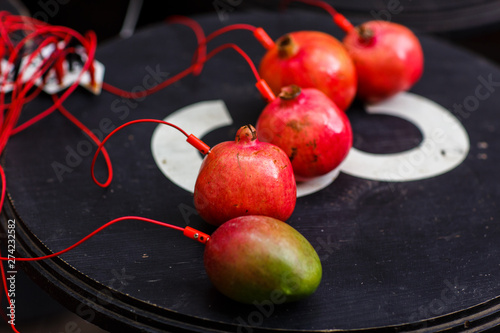 Photo of pomegranates and mangoes with red wires on black table Wallpaper Mural