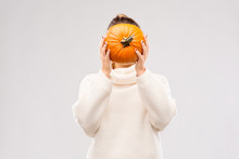 Autumn, Season And Halloween Concept - Woman Holding Pumpkin And Covering Her Face Over Grey Background