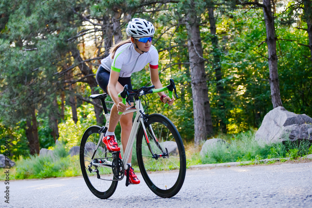 Fototapeta Young Woman Cyclist Riding Road Bicycle on the Free Road in the Forest at Hot Summer Day. Healthy Lifestyle Concept.