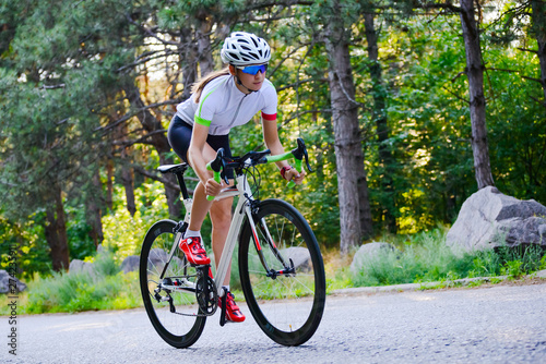 Fotomural  Young Woman Cyclist Riding Road Bicycle on the Free Road in the Forest at Hot Summer Day