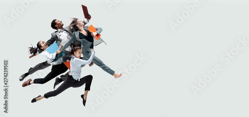 Happy office workers jumping and dancing in casual clothes or suit with folders isolated on studio background Fototapet
