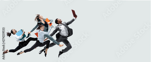 Happy office workers jumping and dancing in casual clothes or suit with folders isolated on studio background. Business, start-up, working open-space, motion and action concept. Creative collage. - 274239533
