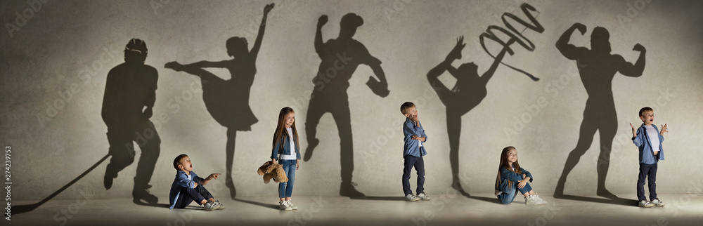 Fototapeta Childhood and dream about big and famous future. Conceptual image with boy and girl and shadows of fit athlete, hockey player, bodybuilder, ballerina. Creative collage made of 2 models.
