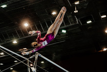 Female Gymnast Leaps To Higher Bar Gymnastics On Black Background And Bright Lamps.