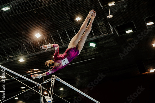 Cuadros en Lienzo  female gymnast leaps to higher bar gymnastics on black background and bright lamps