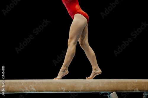 female gymnast in red leotard performance on balance beam on black background Obraz na płótnie
