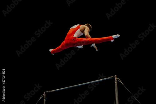 Spoed Fotobehang Gymnastiek artistic gymnastics man gymnast exercise on horizontal bar a black background