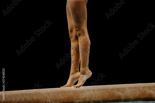 Fotografia  legs female gymnast standing on her tip toes performing on balance beam