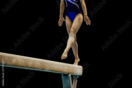 Fotografía  woman gymnast performing on balance beam in black background