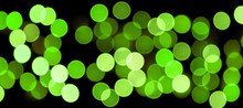 Unfocused Abstract Colourful Bokeh Black Background. Defocused And Blurred Many Round Green Light