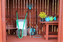 Decorative Shrub Along With Garden Equipment And Tools In A Wooden Shed.