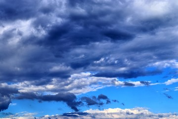 Beautiful mixed white and dark cloud formations on a blue sky