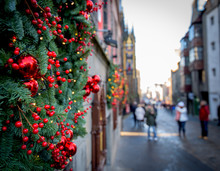 Christmas Tree Decorated On The Wall With Red Balls. Blurred Street In The Background