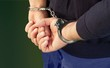 Leinwandbild Motiv Cropped image of male hands in handcuffs behind his back