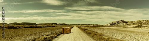 Obraz na plátne Strasse in einer Wüstenlandschaft mit Koffer