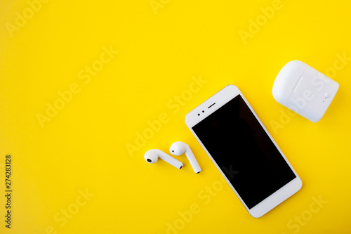 White wireless headphones and smartphone are lying on a bright yellow background. Headphones out of charging case. - 274283128