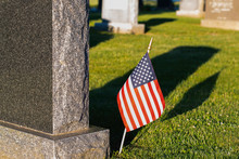 Headstone And American Flag Alone In A Cemetery With Green Grass And Long Shadows.