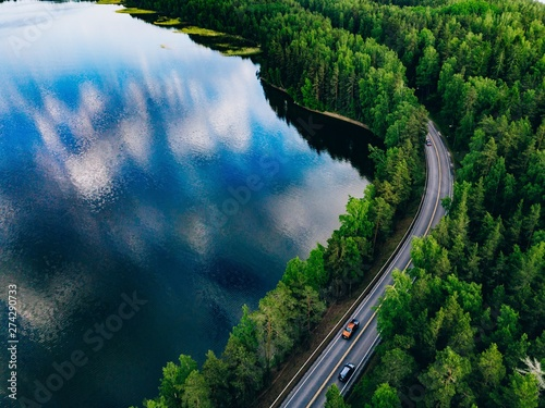 Route dans la forêt Aerial view of road between green forest and blue lake in Finland
