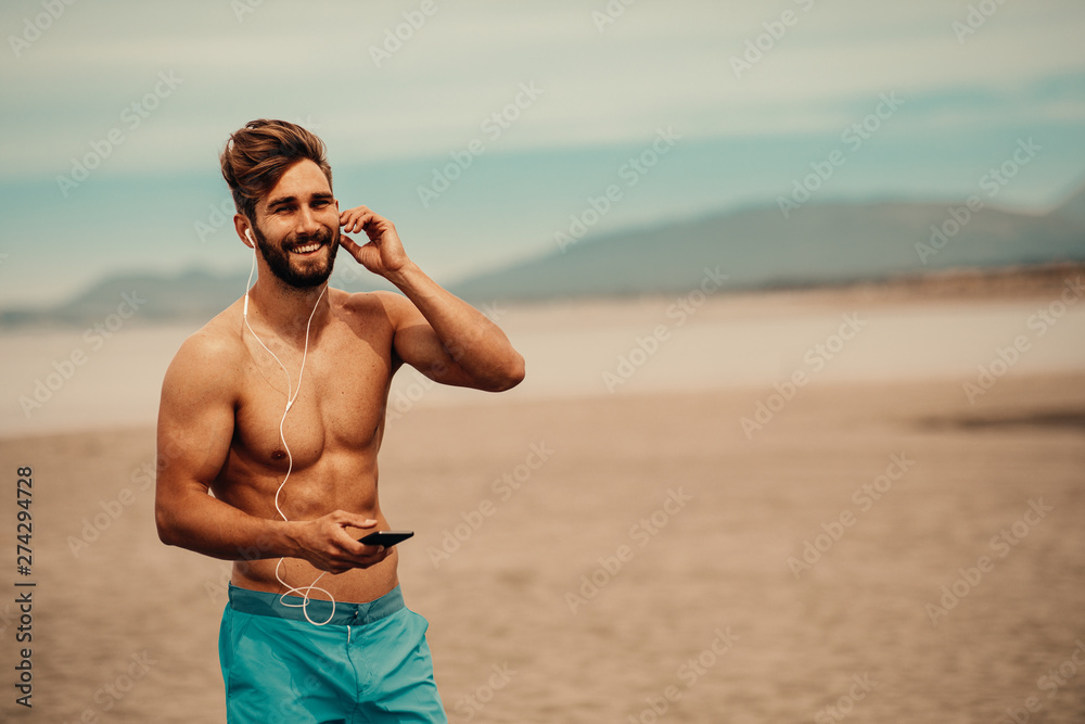 Fototapety, obrazy: Handsome man on the beach listens to music over the earphones