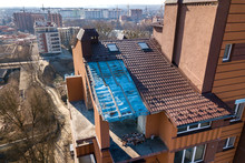 Aerial Top View Of Unfinished Tall Apartment Building, Annex Room Under Construction, High Chimneys And Plastic Windows On Tiled Roof.