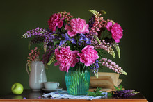 Rustic Still Life With  Bouquet Of Peonies, Irises And Lupins, An Apple And An Book.
