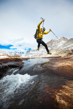 A Man Leaps Across A Rushing Stream In The Titcomb Basin Deep In The Wind River Range In Wyoming.