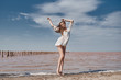 A girl stands on the shore of a beautiful lake. Exquisite photo shoot on the beach.