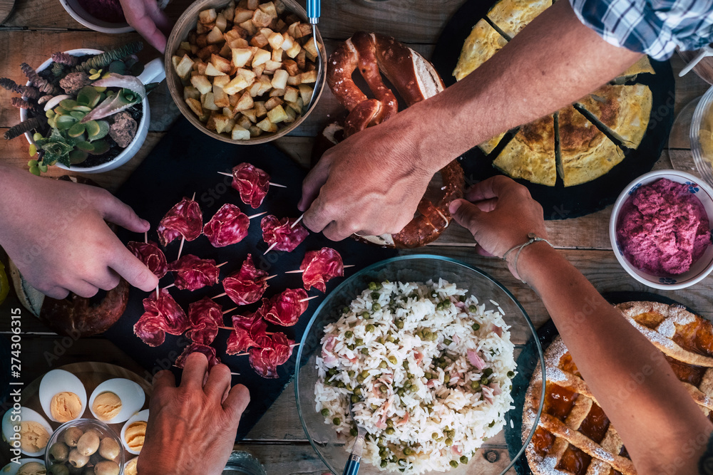 Fototapety, obrazy: Vertical top view of friends eating together  on a wooden table full of food - friendship and celenration people - concept of friendship with adult men and women at home or restaurant