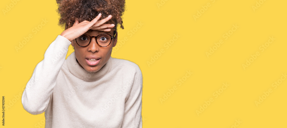 Fototapeta Beautiful young african american woman wearing glasses over isolated background very happy and smiling looking far away with hand over head. Searching concept.