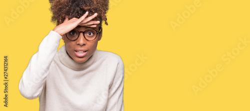 Beautiful young african american woman wearing glasses over isolated background very happy and smiling looking far away with hand over head Fototapet