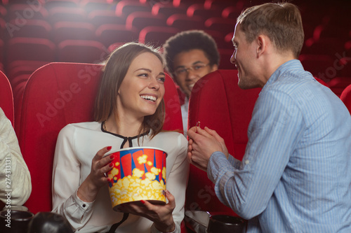 Vászonkép Beautiful woman keeping popcorn in cinema and looking at boyfriend