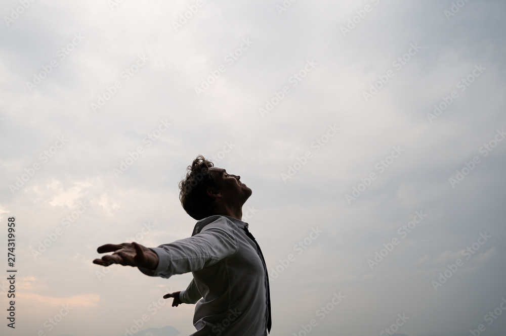 Fototapety, obrazy: Peaceful young businessman standing with his arms spread