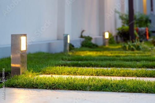 Photo  ground lantern lighting marble walkway in the evening park with a green lawn, closeup lantern illumination warm light marble pavement