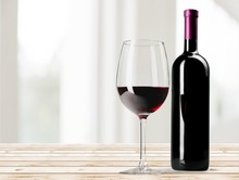 Red Wine Glass On Wooden Desk At Wall Background