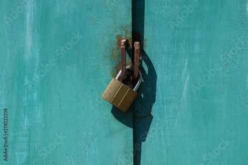 brown padlock hanging on green metal gate outside