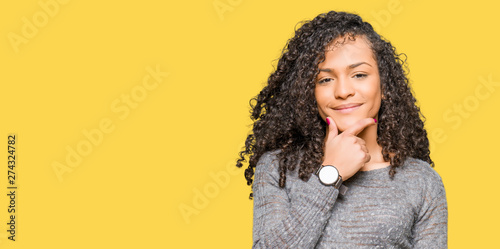 Fotografiet  Young beautiful woman with curly hair wearing grey sweater looking confident at the camera with smile with crossed arms and hand raised on chin