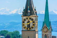 Saint Peter And Fraumünster Church In Zurich (Switzerland) In Front Of Lake Zurich And The Swiss Alps