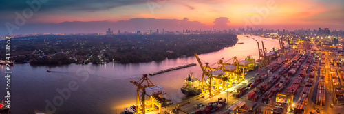 Obraz Logistics and transportation of Container Cargo ship and Cargo plane with working crane bridge in shipyard at sunrise, logistic import export and transport industry background - fototapety do salonu