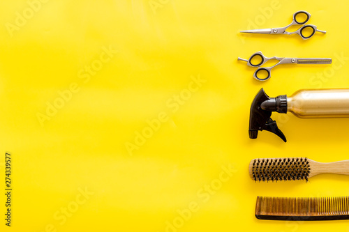 Hairdresser equipment for cutting hair and styling with combs, sciccors, brushes on yellow background top view copyspace