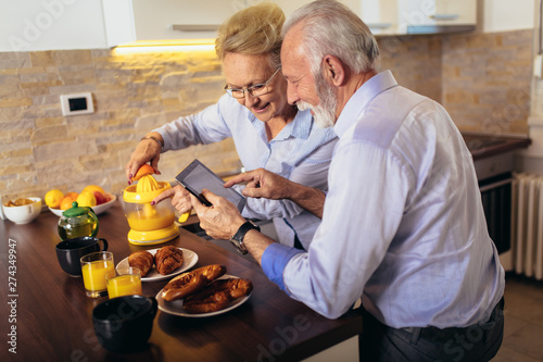 Plakat Aged couple busy look at digital tablet while having delicious breakfast at home kitchen