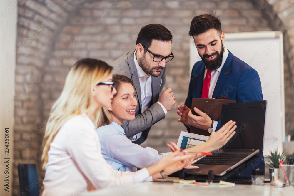 Business colleagues working on laptop in modern office.