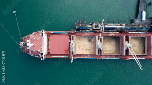 Valokuvatapetti Top down aerial view of Container ship unloading sugar shipment at cargo depot 4