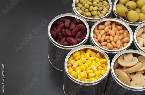 Fotografia, Obraz  Canned green peas, beans, corn, olives and mushrooms on black table