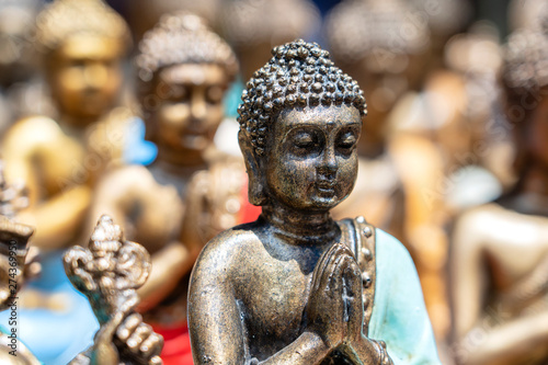 Obraz Buddha statue figures souvenir on display for sale on street market in Bali, Indonesia. Handicrafts and souvenir shop display, close up - fototapety do salonu