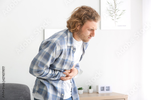 Young man suffering from abdominal pain at home Fototapeta