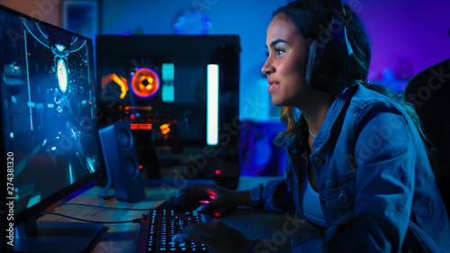 Pretty and Excited Black Gamer Girl in Headphones is Playing First-Person Shooter Online Video Game on Her Computer Canvas Print